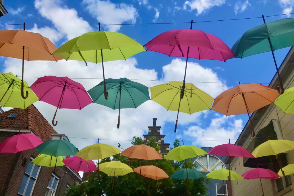 gekleurde parpaplu's boven een terras in Leeuwaren